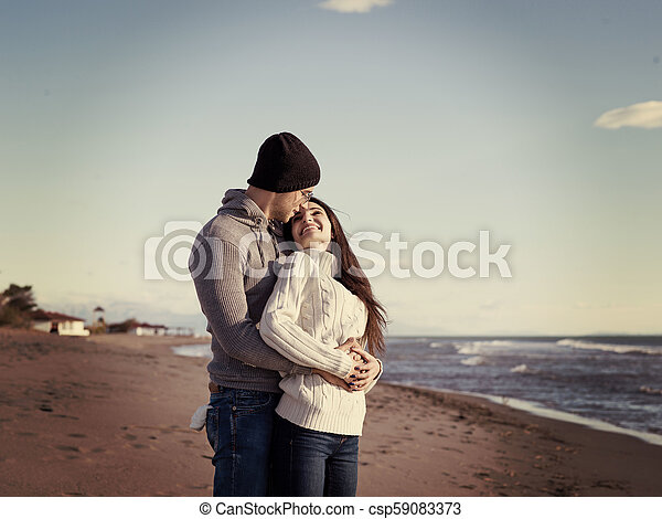 Loving young couple on a beach at autumn sunny day - csp59083373