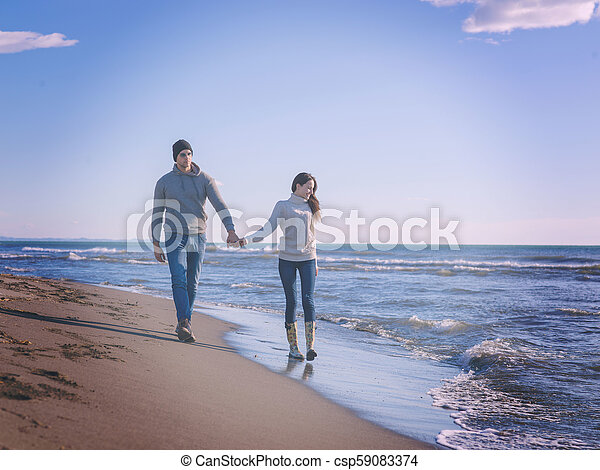 Loving young couple on a beach at autumn sunny day - csp59083374