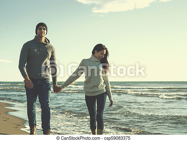 Loving young couple on a beach at autumn sunny day - csp59083375