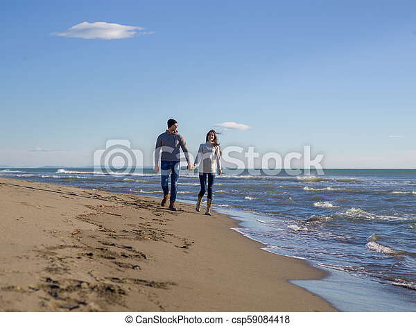 Loving young couple on a beach at autumn sunny day - csp59084418