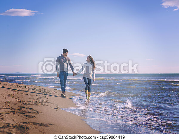 Loving young couple on a beach at autumn sunny day - csp59084419