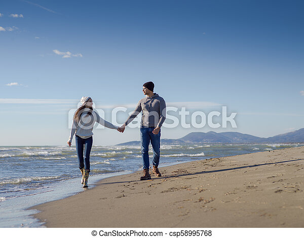 Loving young couple on a beach at autumn sunny day - csp58995768