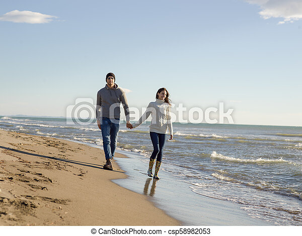 Loving young couple on a beach at autumn sunny day - csp58982053