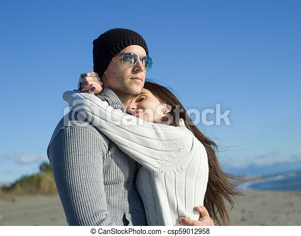 Loving young couple on a beach at autumn sunny day - csp59012958