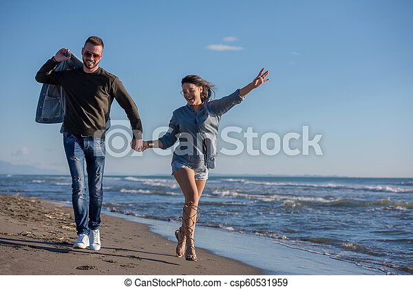 Loving young couple on a beach at autumn sunny day - csp60531959