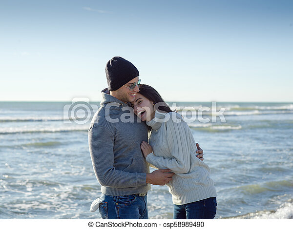 Loving young couple on a beach at autumn sunny day - csp58989490