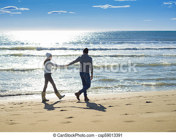 Loving young couple on a beach at autumn sunny day - csp59013391