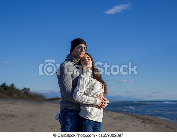 Loving young couple on a beach at autumn sunny day - csp59082897