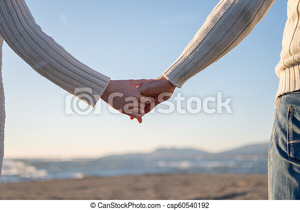 Loving young couple on a beach at autumn sunny day - csp60540192