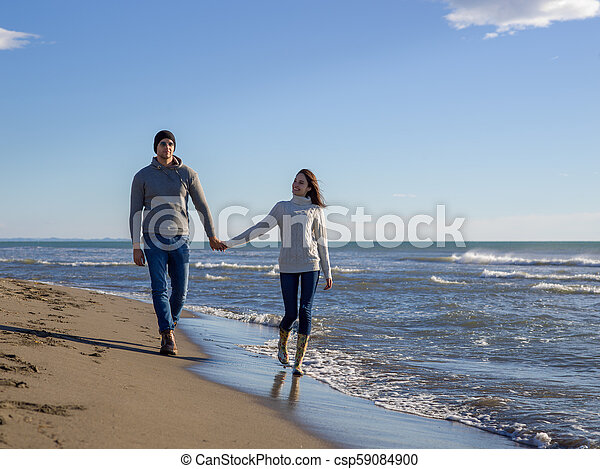 Loving young couple on a beach at autumn sunny day - csp59084900