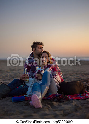 Loving Young Couple Sitting On The Beach beside Campfire drinking beer - csp59090099