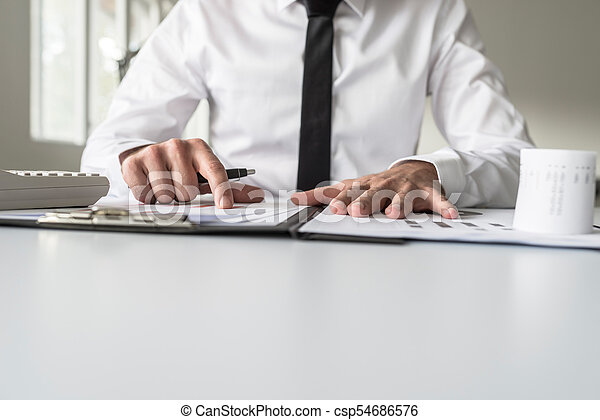 Low angle view of a businessman pointing to an analytical graph - csp54686576