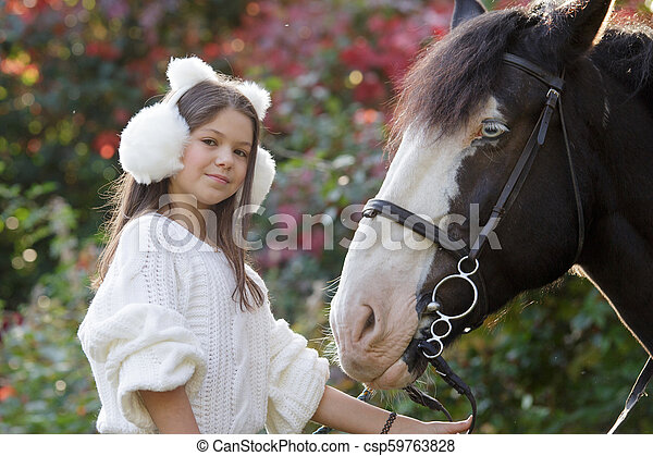 Low angle view of a happy female horseback rider sitting on a horse - csp59763828