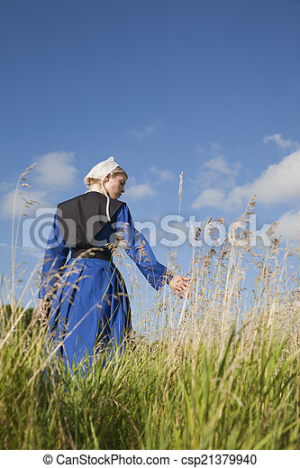 Low angle view of Amish girl walking in a field - csp21379940