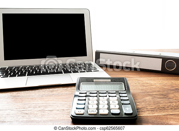 low angle view of calculator, laptop and file folder on wooden desk - csp62565607