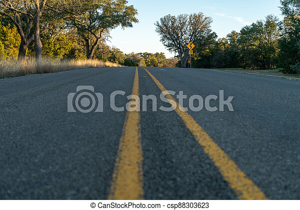 Low Angle View of Country Road With Traffic Sign on the Right - csp88303623