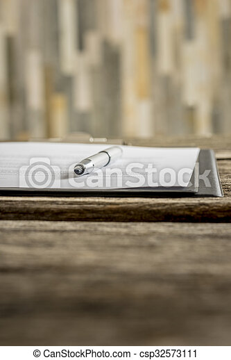 Low angle view of ink pen lying on a document in folder - csp32573111