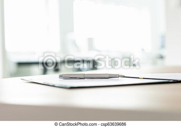 Low angle view of ink pen lying on document - csp63639686