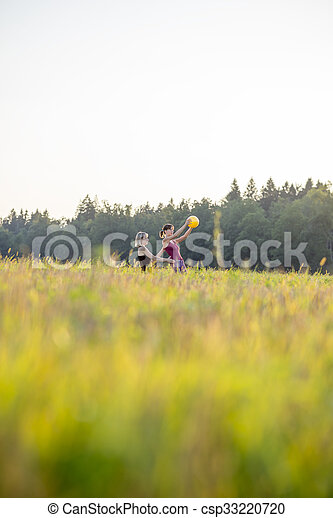 Low angle view of pilates trainer and trainee working out with a yellow ball outside in nature - csp33220720
