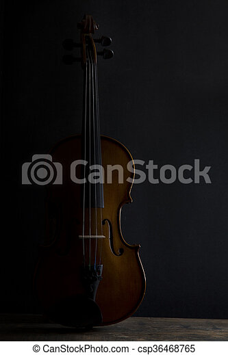 Low key violin in vertical position with side lighting - csp36468765