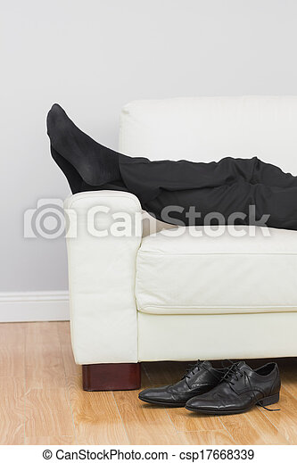 Low section of businessman resting on sofa in living room - csp17668339