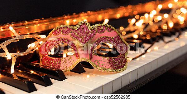 Máscara de carnaval y luces en un teclado de piano - csp52562985