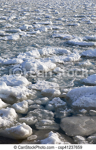 Lumps of snow and ice frazil on the surface of the freezing river water in early winter - csp41237659