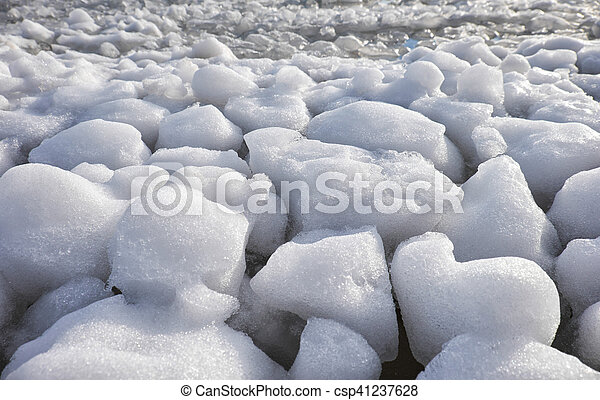 Lumps of snow and ice frazil on the surface of the freezing river water in early winter - csp41237628