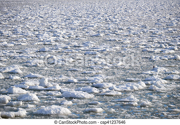 Lumps of snow and ice frazil on the surface of the freezing river water in early winter - csp41237646