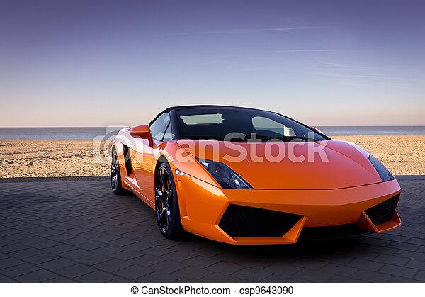 Luxurious orange sports car near beach - csp9643090