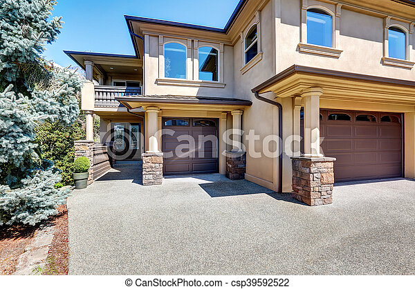luxury house exterior with columns and brown garage doors stock photo - Luxury House Exterior