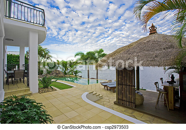 luxury mansion outside deck with Bali hut, bar and pool - csp2973503