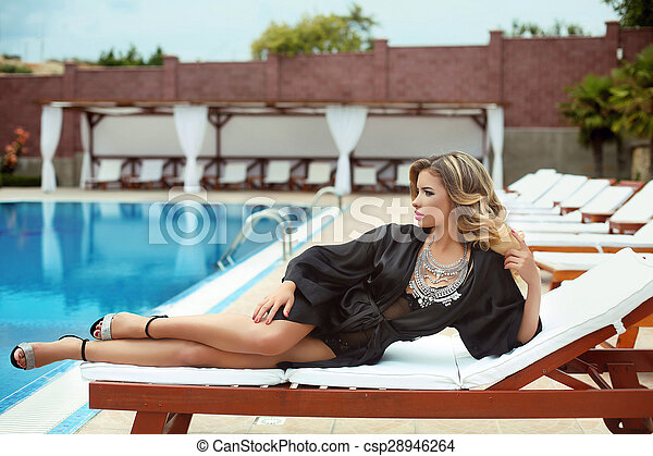 b5ca01440f8 Luxury resort sexy girl model in fashion clothes relaxing on beach bed by  swim pool. attractive blond girl model posing near swimming pool