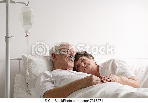 Lying next to sick husband - csp47318271