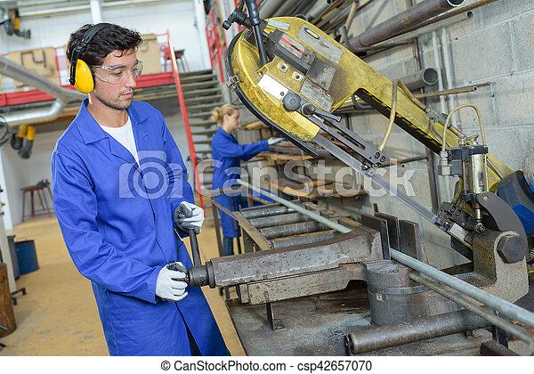 Trabajador atendiendo una máquina - csp42657070