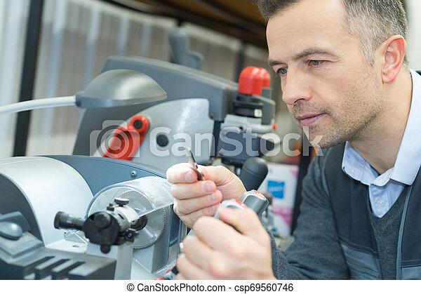 Cobbler haciendo copia de la llave en la máquina - csp69560746