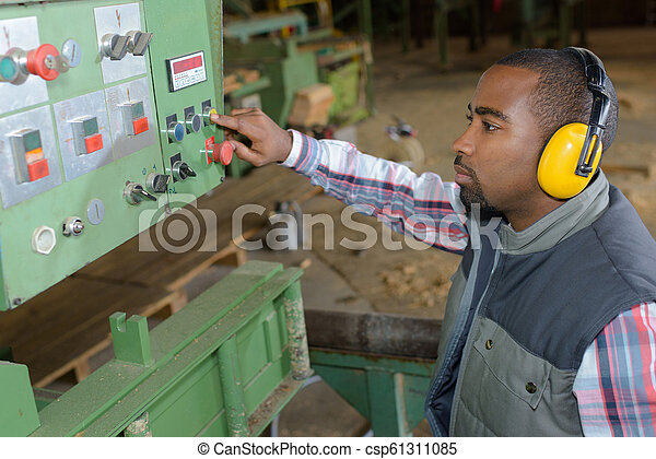 El hombre que controla la máquina industrial - csp61311085