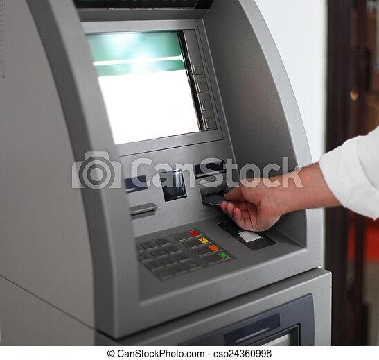Un hombre usando una máquina bancaria - csp24360998