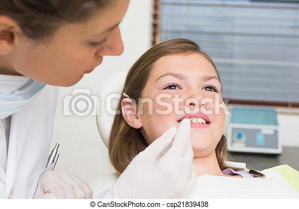 Kinderarzt, der kleine Mädchenzähne in den Zahnärzten untersucht - csp21839438