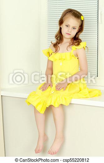 Ein kleines Mädchen sitzt mit Jalousie am Fenster - csp55220812