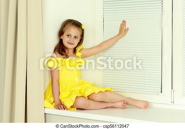 Ein kleines Mädchen sitzt mit Jalousie am Fenster - csp56112047