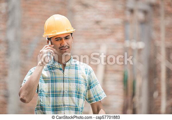 Trabajador de construcción usando teléfono móvil - csp57701883
