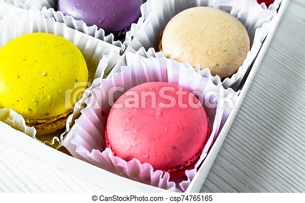 Macarons isolated on a white wooden background... - csp74765165