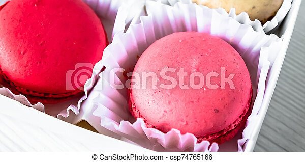 Macarons isolated on a white wooden background... - csp74765166