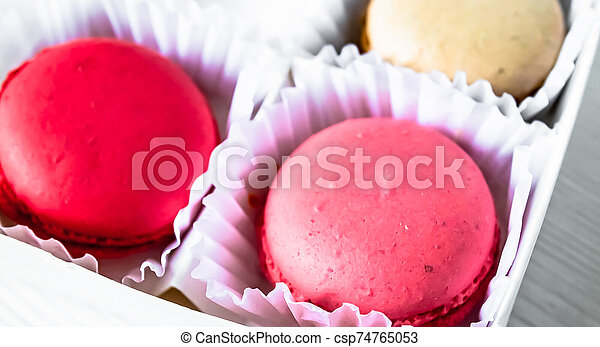 Macarons isolated on a white wooden background... - csp74765053
