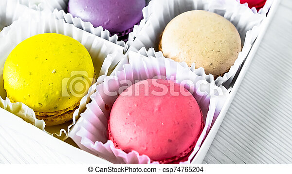 Macarons isolated on a white wooden background... - csp74765204