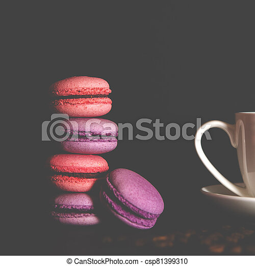 Macarons with a white cup of coffee on a black background. - csp81399310