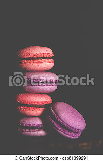 Macarons with a white cup of coffee on a black background. - csp81399291