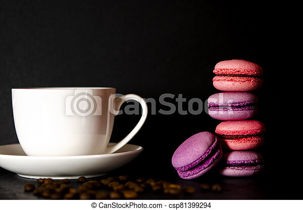 Macarons with a white cup of coffee on a black background. - csp81399294