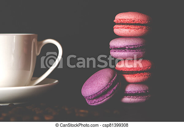 Macarons with a white cup of coffee on a black background. - csp81399308